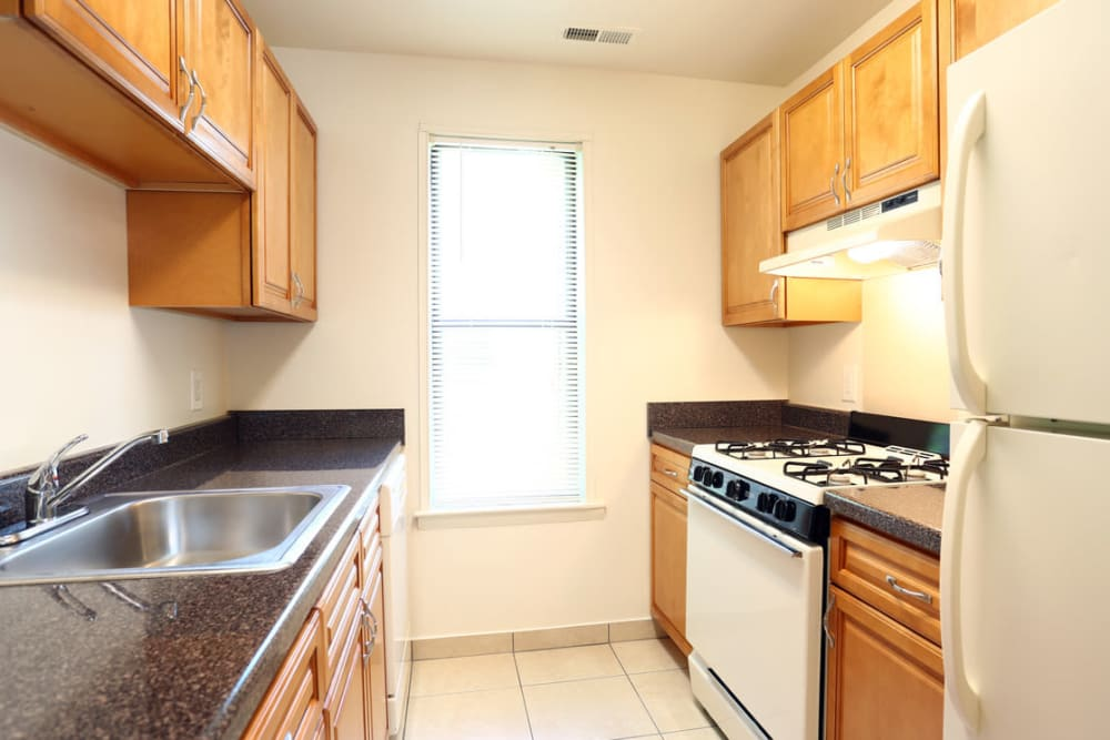 Kitchen with wooden cabinets at Laurel Hill Apartments in Lindenwold, New Jersey