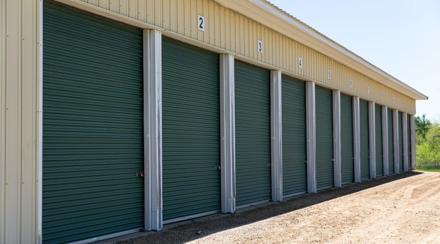 Storage units with green doors and locks at KO Storage of Tomah - Townline in Tomah, Wisconsin