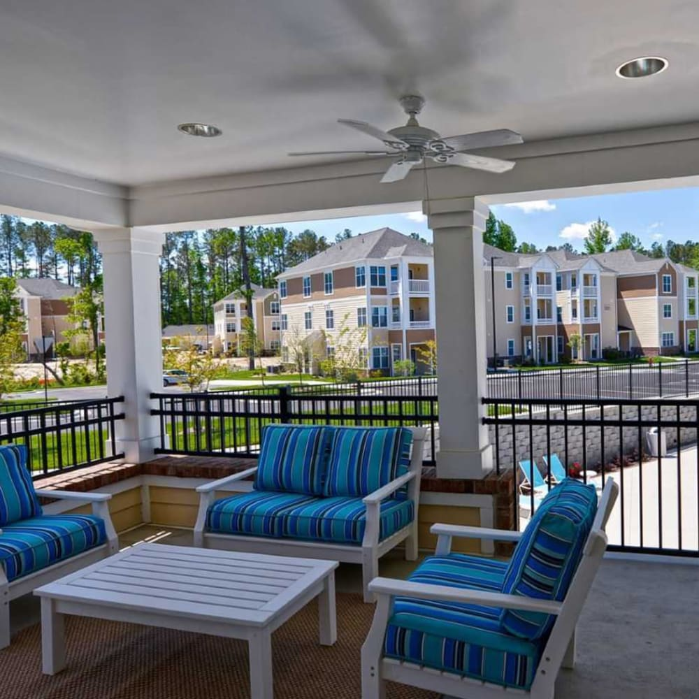 Nice outdoor covered area with comfy chairs to relax in at The Reserve at White Oak in Garner, North Carolina