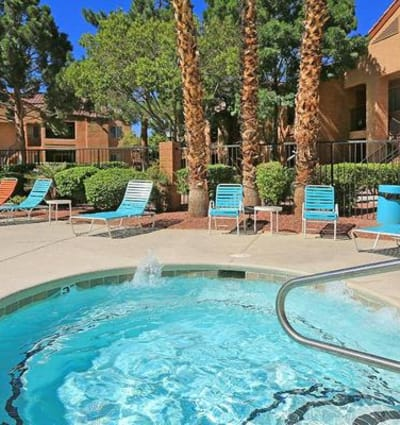 Lounge chairs and mature trees near the spa at Alterra Apartments in Las Vegas, Nevada