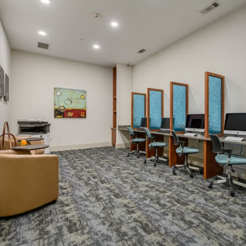 Executive business center with multiple workstations and commercial printer at Sabina in Austin, Texas