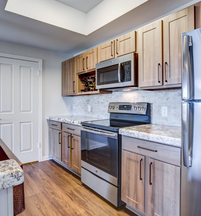 Granite countertops, stainless-steel appliances, and gorgeous wood cabinets and floor in model home kitchen at Riata Austin in Austin, TX