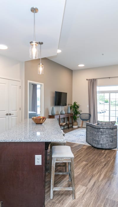 Open-concept kitchen with an island looking into the living area of a model home at The Station at River Crossing in Macon, Georgia