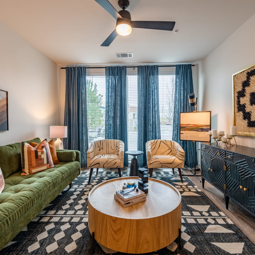 Model living room with ceiling fan and floor to ceiling windows at The Langford in Dallas, Texas