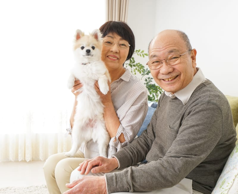 Resident couple pose for the camera with their dog  at The Sanctuary at St. Cloud in St. Cloud, Minnesota