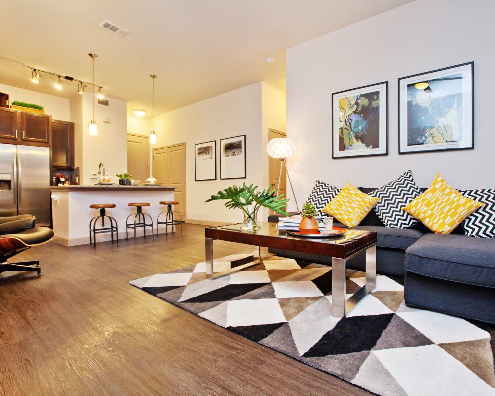 Wood-style vinyl flooring in a model living room at Olympus Auburn Lakes in Spring, Texas