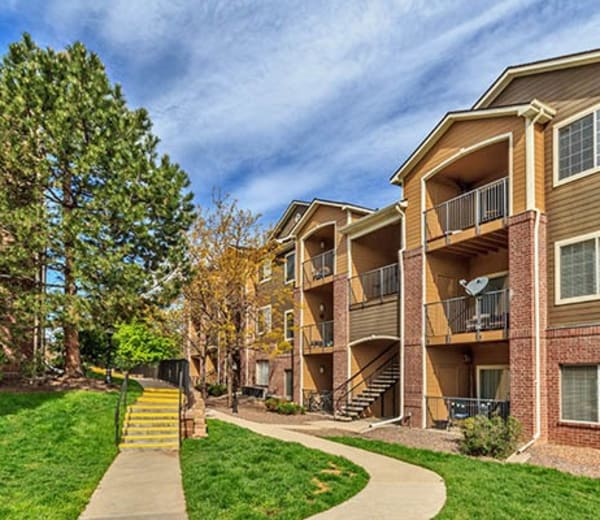 Exterior building shot, grass and trees at Arapahoe Club Apartments in Denver