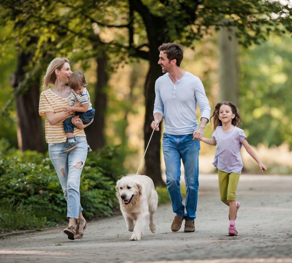 Family walking their dog through a park in Stockbridge, Georgia near 900 Dwell