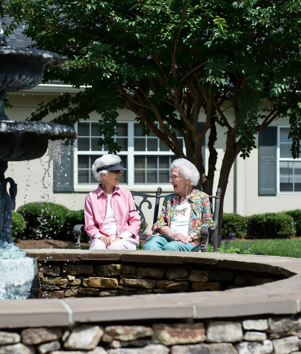 Two residents sitting outside talking at Azalea Estates of Fayetteville in Fayetteville, Georgia