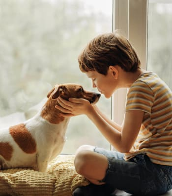 A young resident kissing his dog on the nose at Deer Valley Apartment Homes in Roseville, California