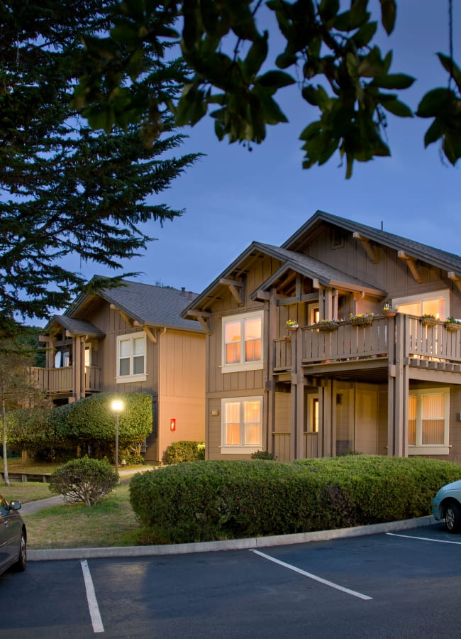 Exterior of the building at dusk at Seventeen Mile Drive Village Apartment Homes in Pacific Grove, California