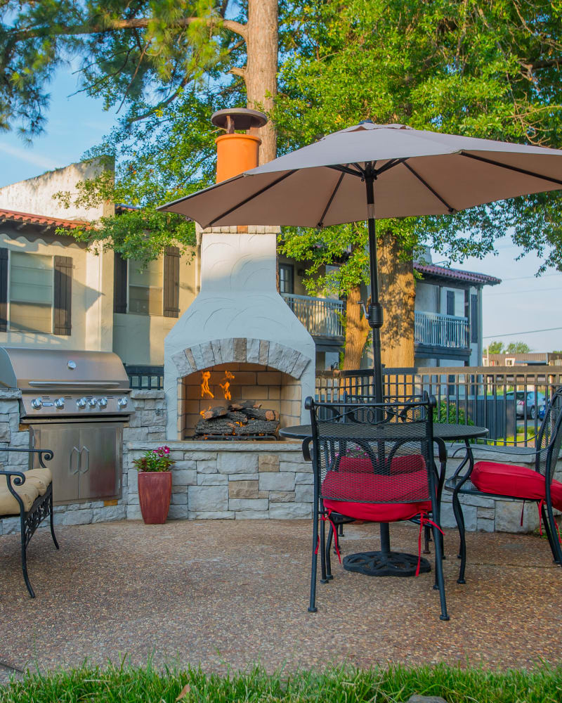 Outdoor patio area with a fireplace at Barcelona Apartments in Tulsa, Oklahoma