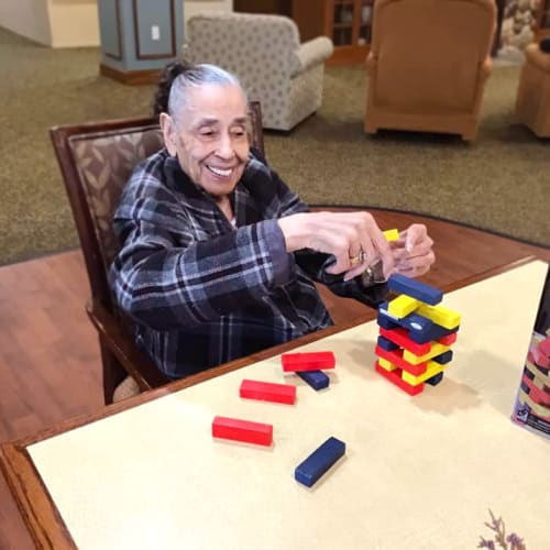 Resident playing jenga at Oxford Glen Memory Care at Grand Prairie in Grand Prairie, Texas