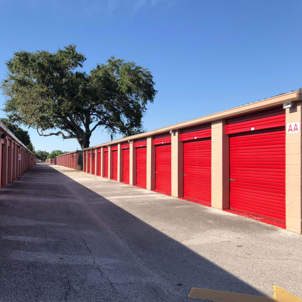 Outdoor storage units with red doors at StorQuest Self Storage in Tampa, Florida