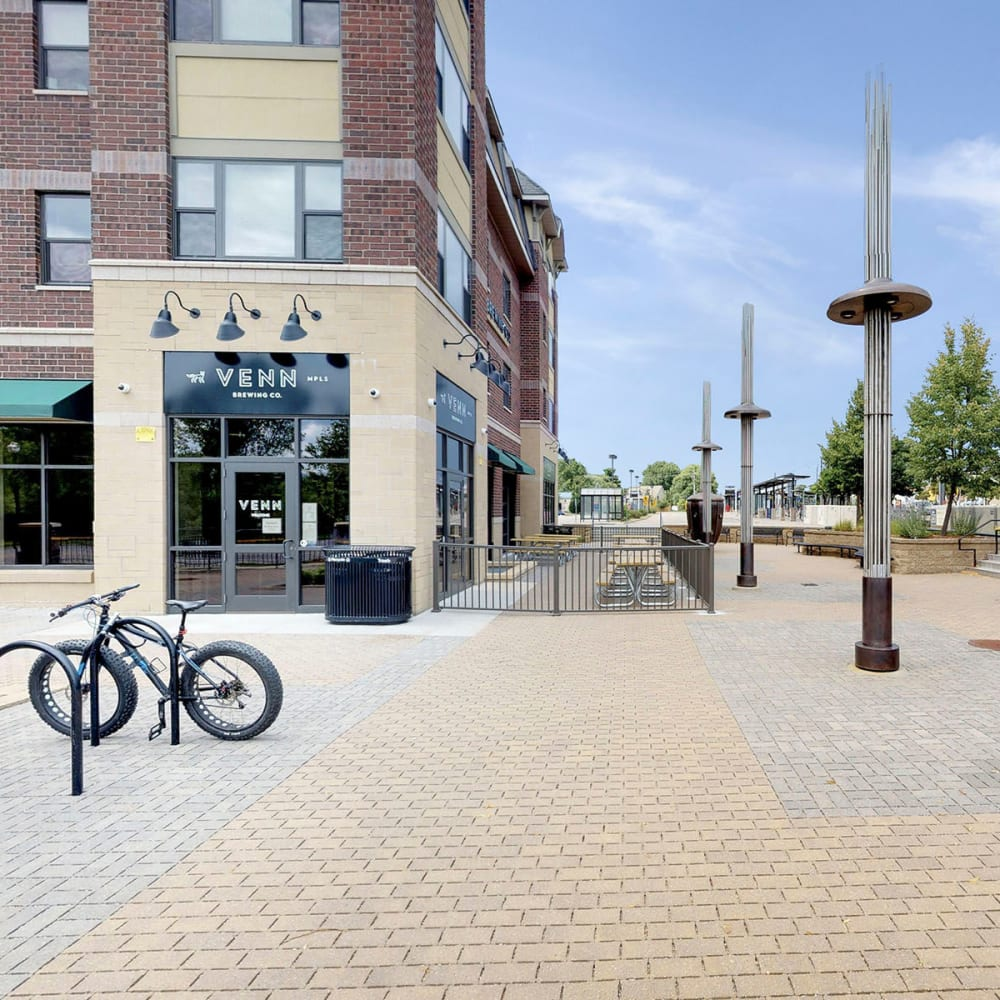 Retail shops at street level with cobblestone sidewalks outside at Oaks Station Place in Minneapolis, Minnesota