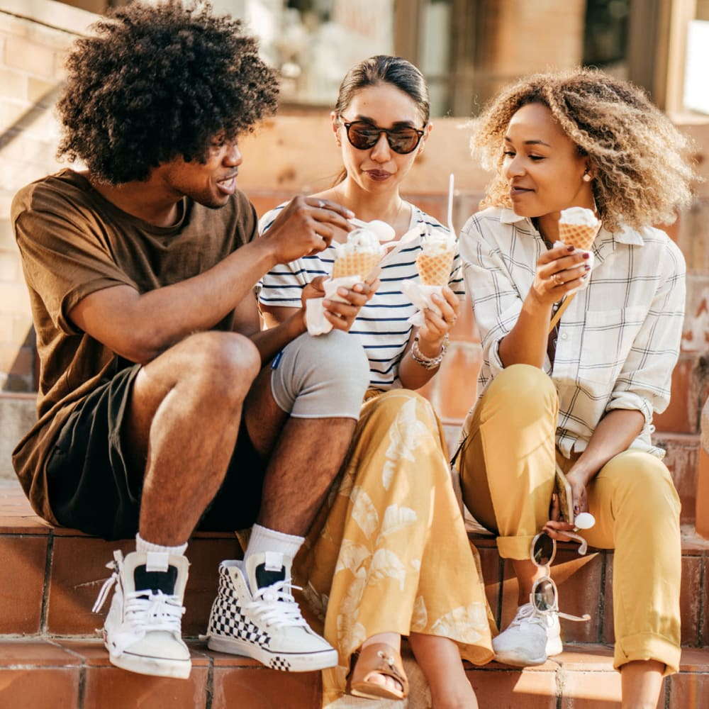 Resident friends on a downtown stoep enjoying ice cream near Oaks Station Place in Minneapolis, Minnesota