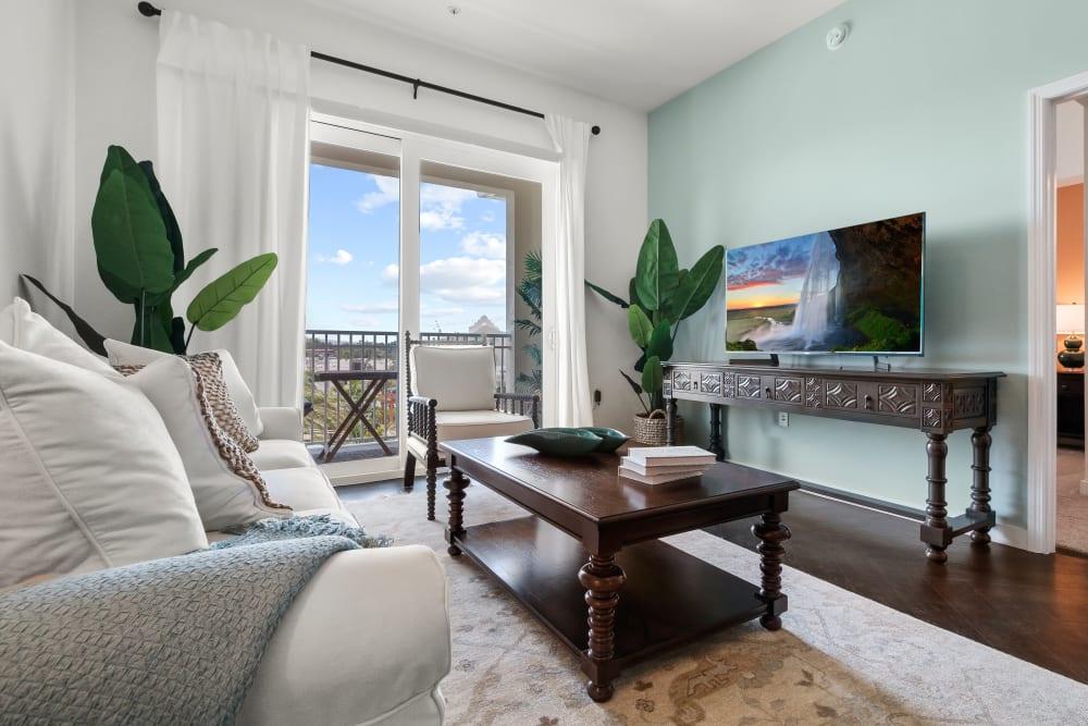 Model living room opening onto a private balcony at Town Lantana in Lantana, Florida