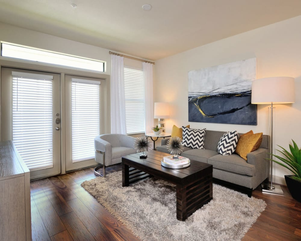 Open-concept model home's living room with hardwood floors at Olympus Falcon Landing in Katy, Texas