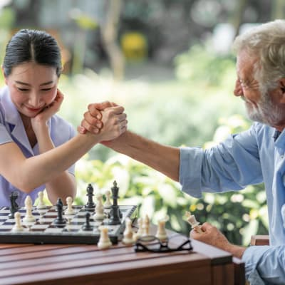 Resident and caregiver playing chess at The Sanctuary at Brooklyn Center in Brooklyn Center, Minnesota