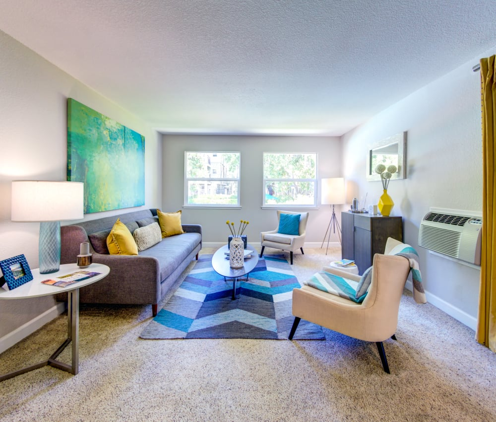 Model living room with plush carpeting and modern furnishings at Sofi Sunnyvale in Sunnyvale, California