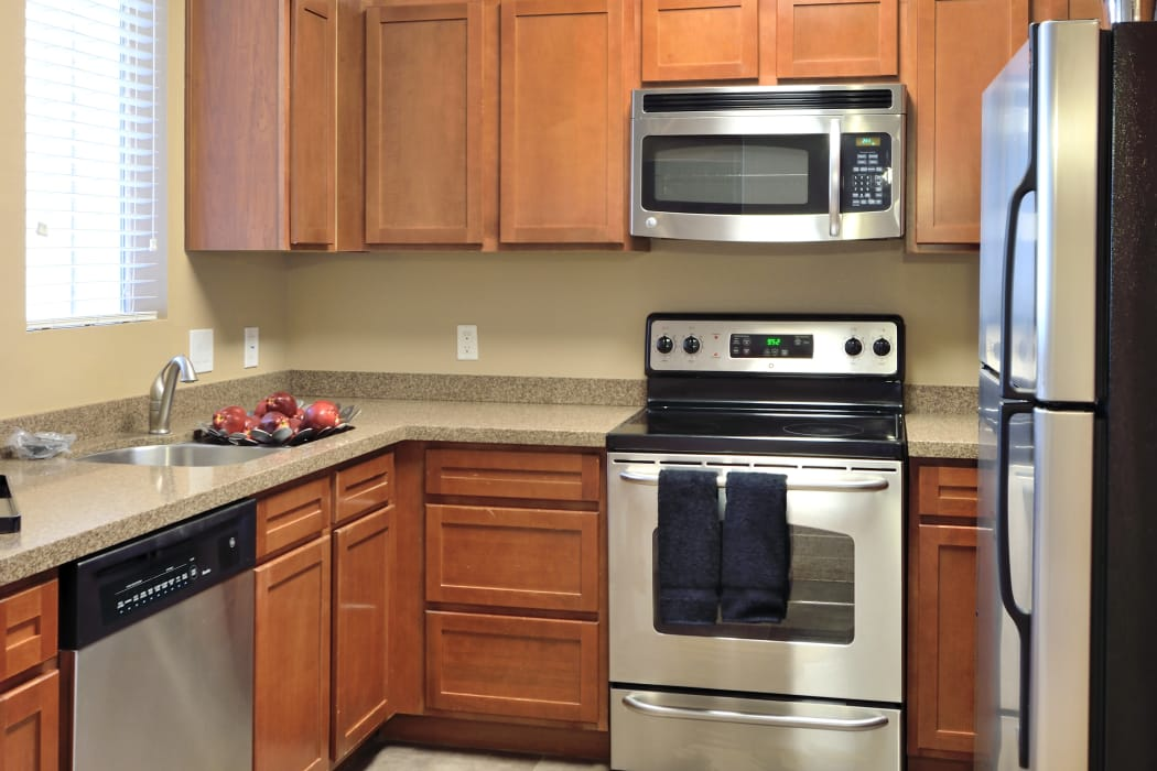 Modern kitchen with stainless-steel appliances in model home at Lumiere Chandler in Chandler, AZ