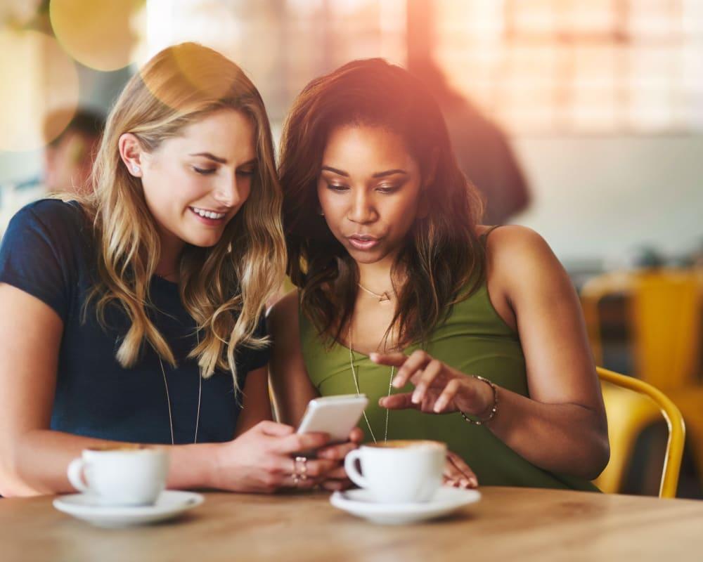 Friend getting coffee together near Hillsborough Plaza Apartments in San Mateo, California