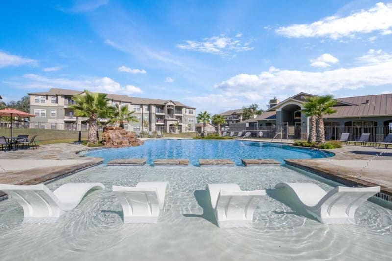 Resort style swimming pool with lounge chairs in the shallow end at Verandas at Alamo Ranch in San Antonio, Texas