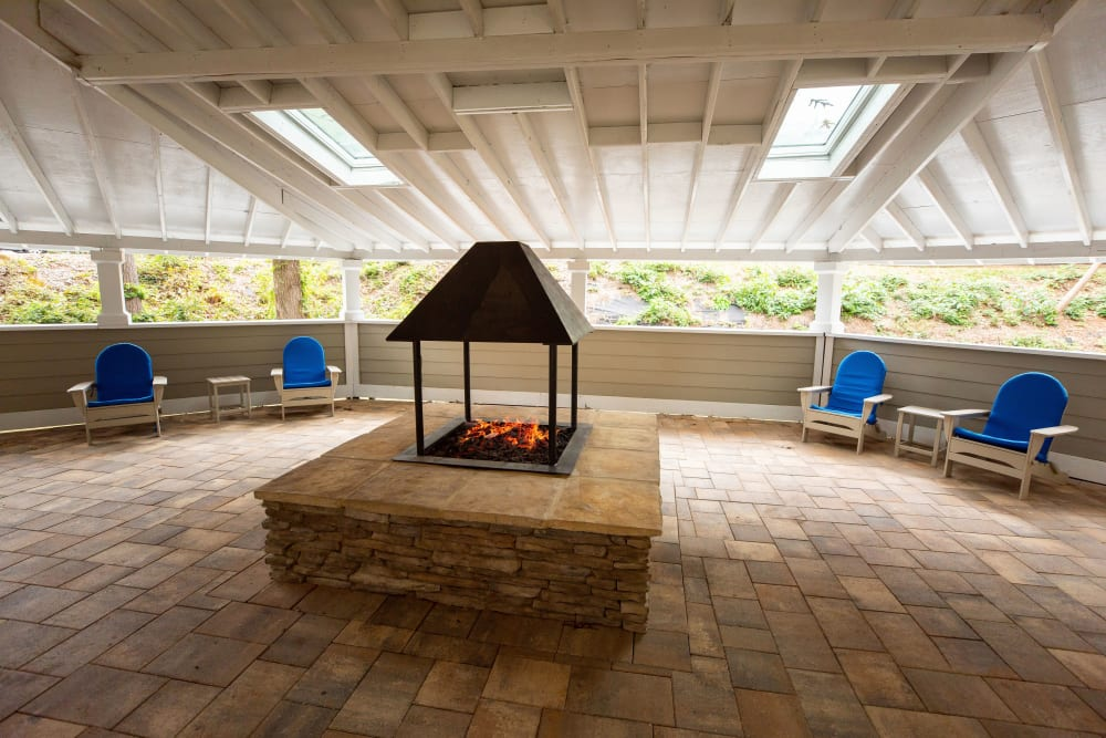 A covered area with a firepit and chairs at The Corners at Crystal Lake in Winston Salem, North Carolina