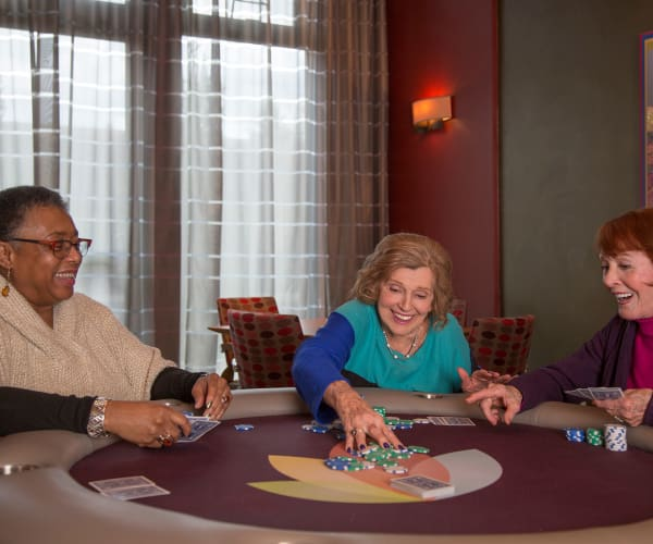 Residents playing a game of cards at All Seasons Naples in Naples, Florida