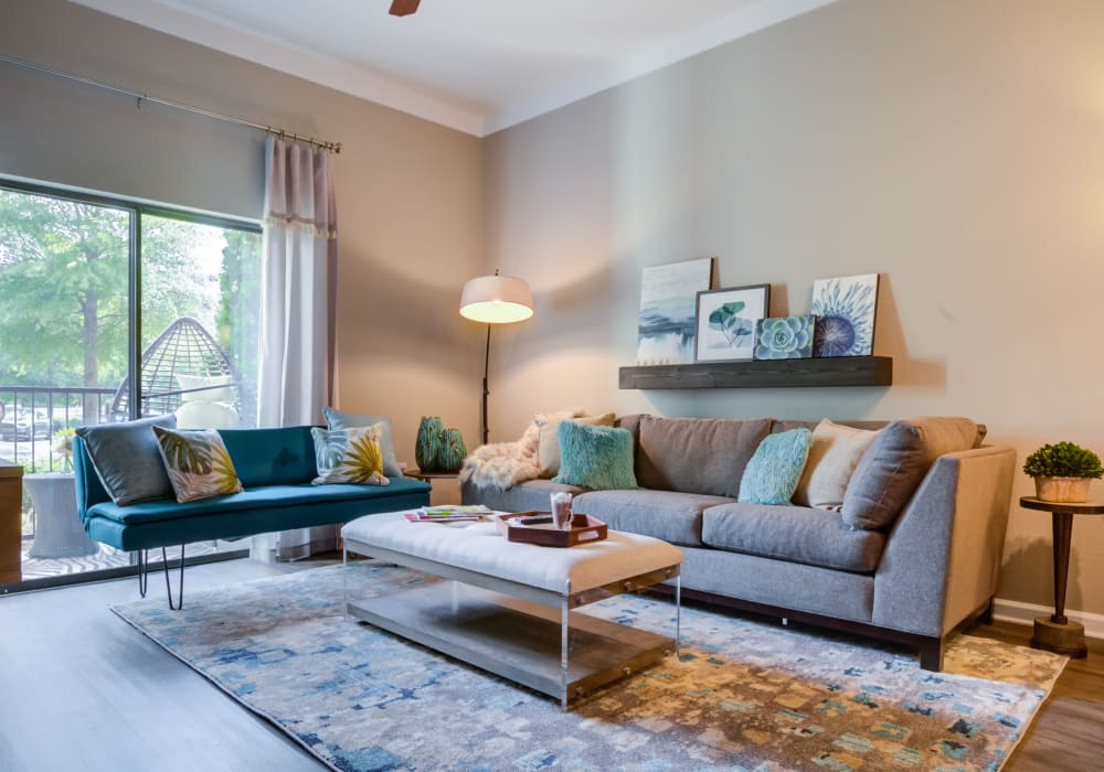 Well-decorated open-concept living space with natural light at Celsius Apartment Homes in Charlotte, North Carolina