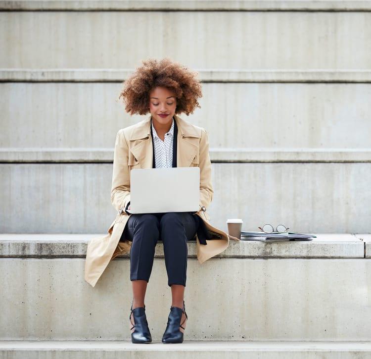 Resident working on her laptop outside her office near Verse Seattle in Seattle, Washington