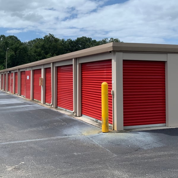 Outdoor storage units with red doors at StorQuest Self Storage in Odessa, Florida