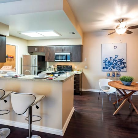 Brown Renovated Kitchen with Dining Room View and Bar top seating  at Sierra Del Oro Apartments