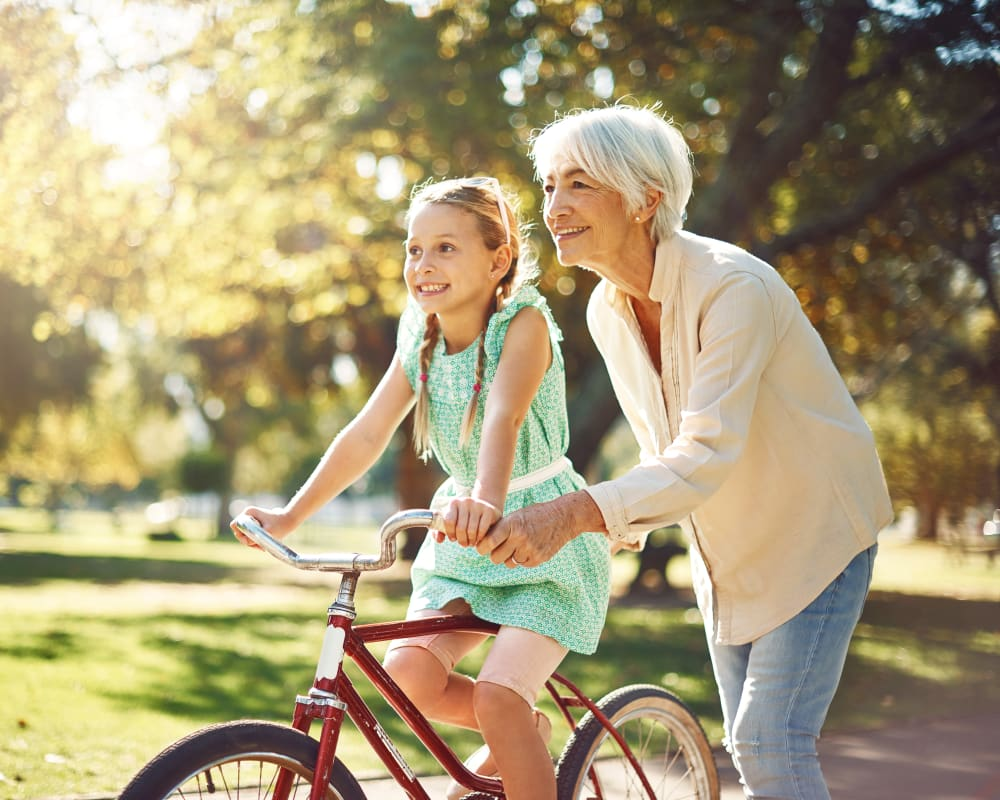 Senior with Granddaughter on bike at The Palisades at Broadmoor Park in Colorado Springs, Colorado