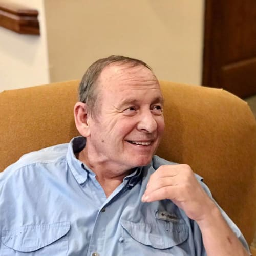 Resident smiling and sitting in a chair at Oxford Glen Memory Care at Carrollton in Carrollton, Texas