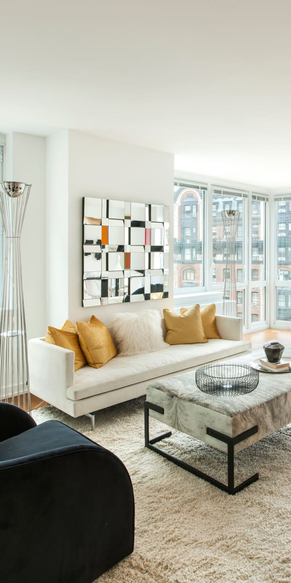 Spacious living room with all-around city views at The Larstrand in New York, New York