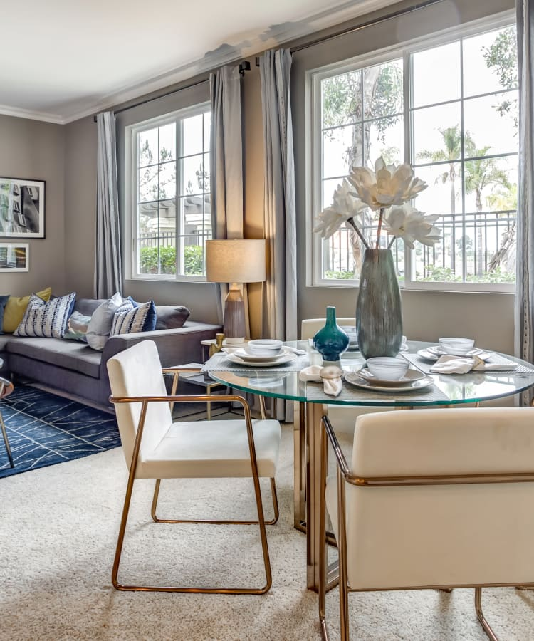 Open-concept living and dining areas with plush carpeting and accent walls in a model home at Sofi Highlands in San Diego, California