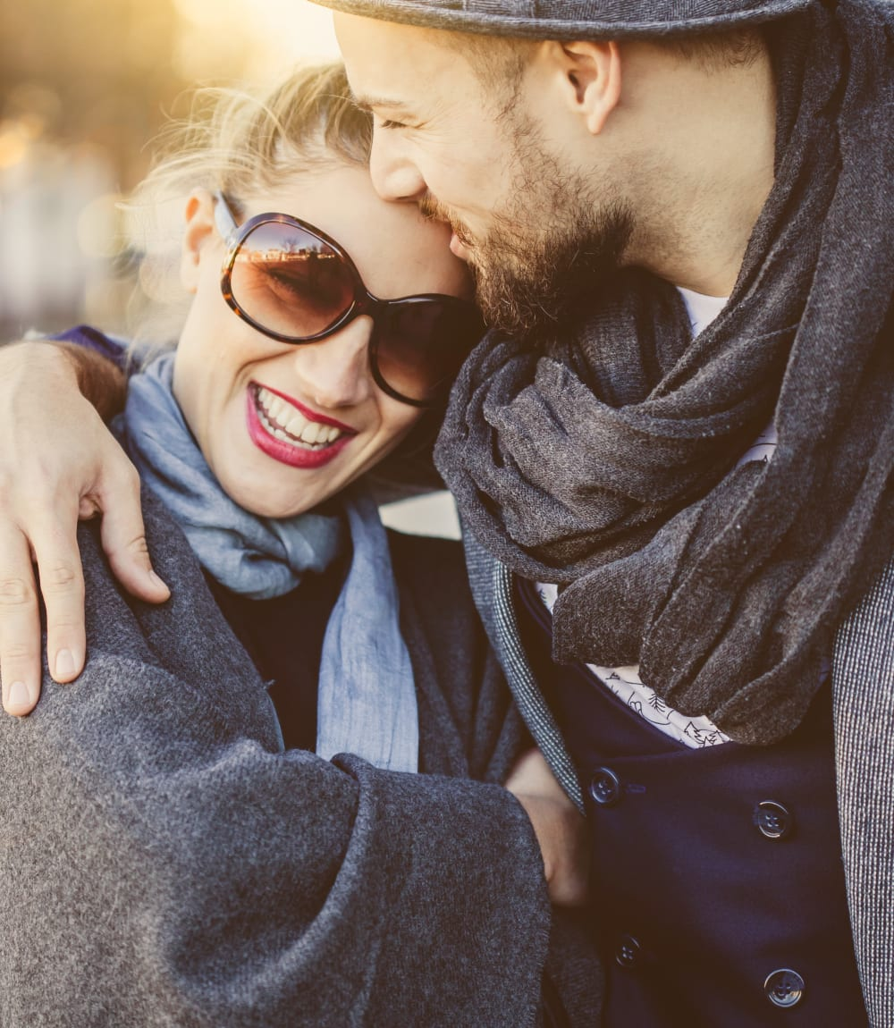 Resident couple hugging each other and smiling as they walk through the neighborhood near Sofi at Morristown Station in Morristown, New Jersey