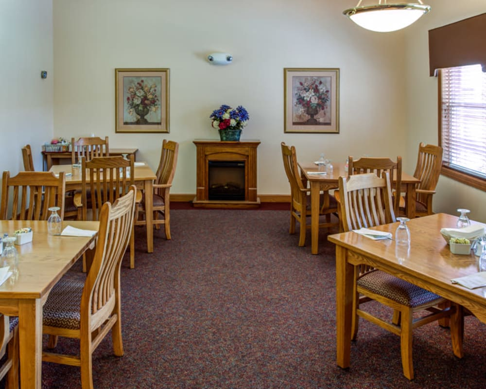 Intimate resident dining room with fireplace at Prairie Hills in Clinton, Iowa.