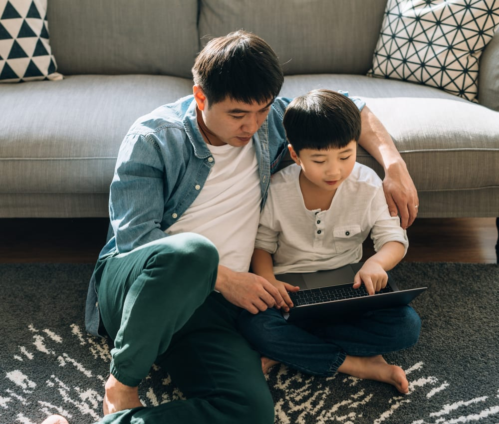 Resident father helping his son do schoolwork on a laptop in their new home at Sofi at Cedar Mill in Portland, Oregon