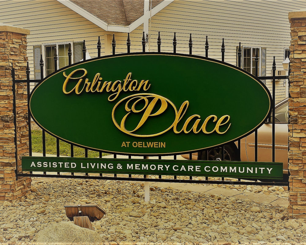 Signage in a bed of rocks at Arlington Place Oelwein in Oelwein, Iowa.