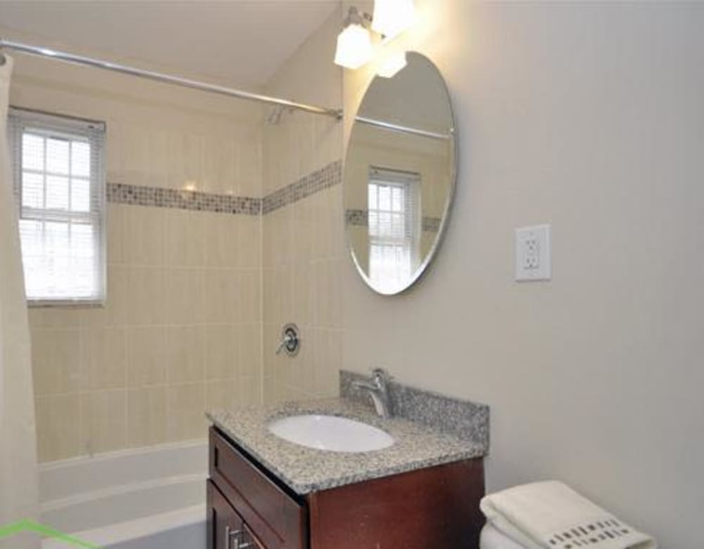 Bathroom with cut vanity and circle mirror next to the shower at Eagle Rock Apartments at Maplewood in Maplewood, New Jersey