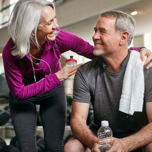Residents taking a break from their workout to chat in the fitness center at The Pointe at Siena Ridge in Davenport, Florida