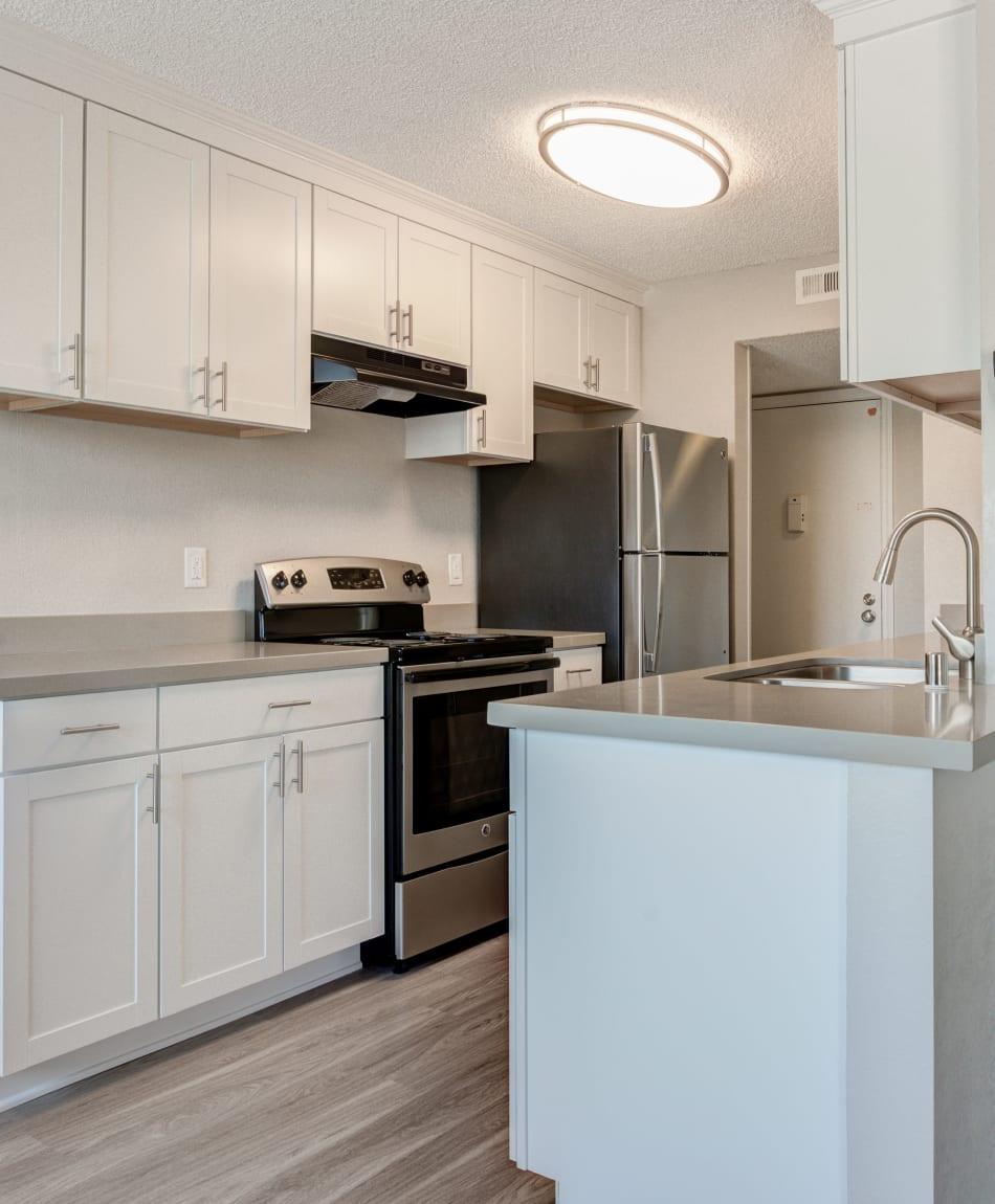 Modern kitchen with sleek, stainless-steel appliances in a model home at Veranda La Mesa in La Mesa, California