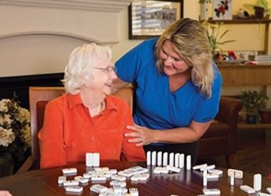 Caregiver and resident talking about dominos at Burr Ridge Senior Living in Burr Ridge, IL