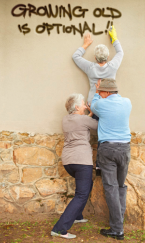 Group of seniors spray painting motivational words on the wall outside a community by Legacy Affordable Retirement Communities in Bellevue, Washington