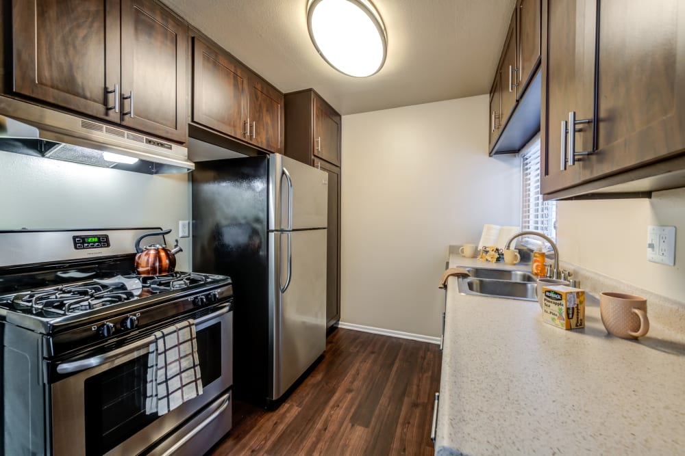 Kitchen with wood-style flooring at Kendallwood Apartments in Whittier, California