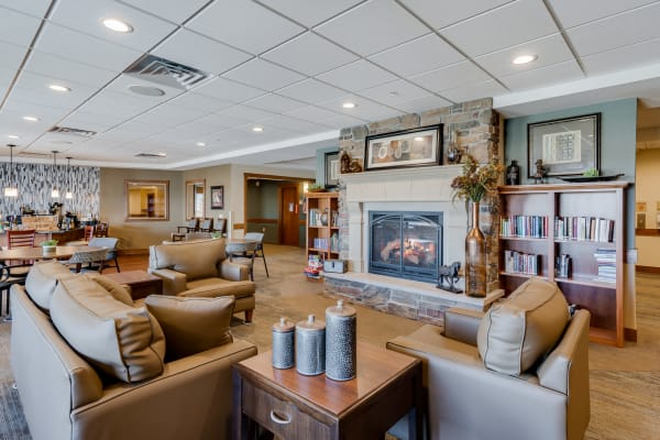 Community gathering space with leather couches and fireplace at Arbor Glen Senior Living in Lake Elmo, Minnesota