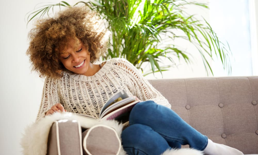 Resident on her couch reading a book in her living room at River Villas in Palmyra, New Jersey