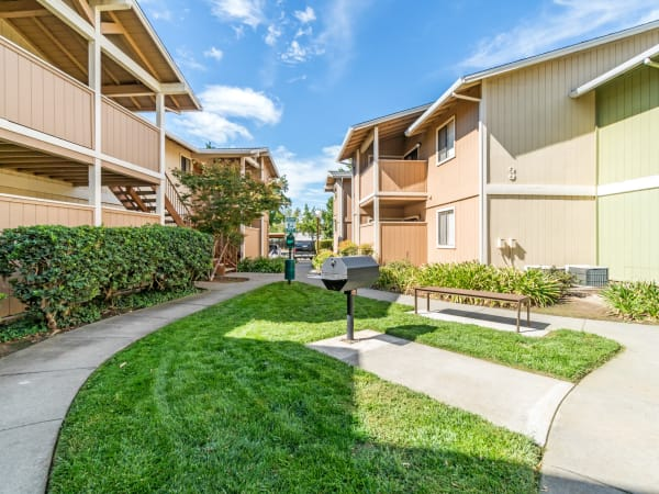 Exterior Building and Walkway shot with BBQ and Lush landscaping Sommerset Apartments in Vacaville
